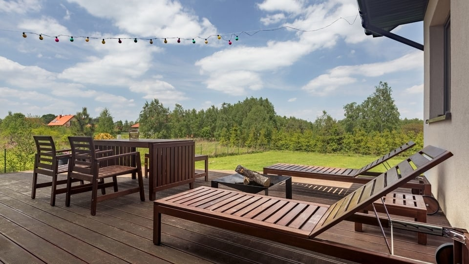 an outdoor deck with lawn chairs at Bunbury Patios